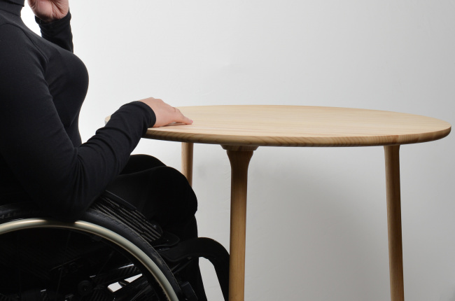 There is wooden table with three thin legs besides there is women in a manual wheelchair